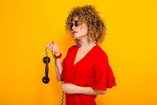 Atrakcyjna Kobieta Z Krótkimi Kręconymi Włosami Z Telefonem Premium Zdjęcia