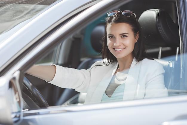 Atrakcyjna Młoda Kobieta Jedzie Samochód. Fantazyjna Kobieta W Samochodzie. Bogata Dorosła Kobieta W Samochodzie. Pewna Kobieta Premium Zdjęcia