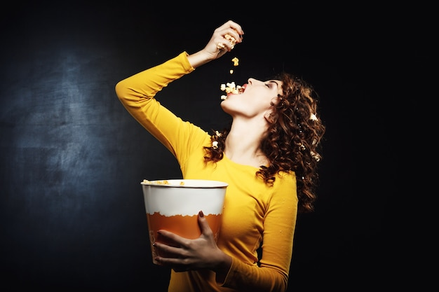 Atrakcyjna Młoda Kobieta Leje Popcorn W Ustach, Trzymając Duże Wiadro Darmowe Zdjęcia