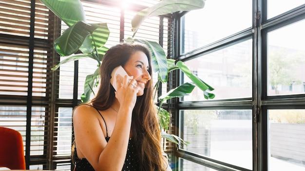 Atrakcyjna młoda kobieta opowiada na mądrze telefonie Darmowe Zdjęcia