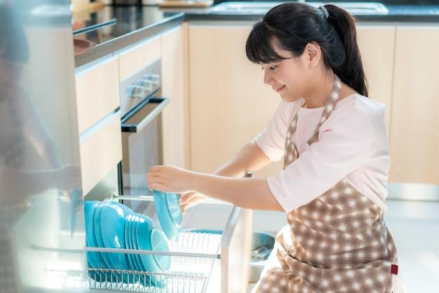 Atrakcyjna Młoda Kobieta Z Azji ładuje Zmywarkę Do Szafek W Kuchni Podczas Sprzątania W Domu Podczas Pobytu W Domu, Korzystając Z Wolnego Czasu Na Codzienne Czynności Porządkowe. Premium Zdjęcia
