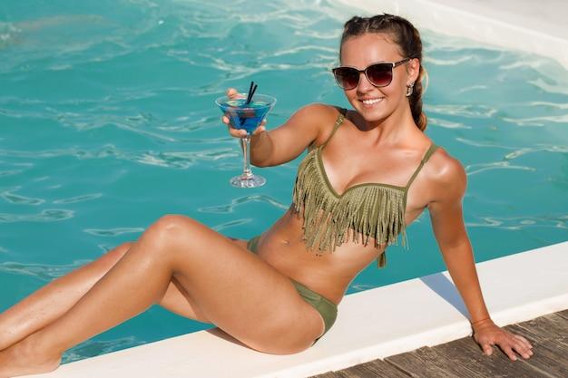 Atrakcyjna młoda opalona kobieta siedzi przy basenie, ciesząc się picia koktajlu Premium Zdjęcia
