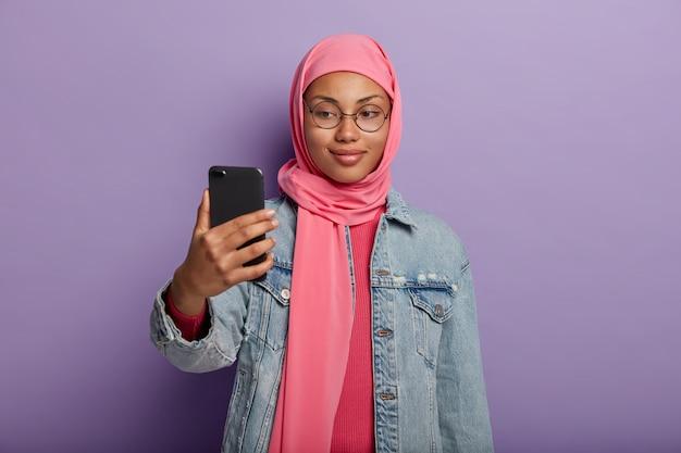Atrakcyjna Muzułmanka Z Małym Uśmiechem Robi Sobie Zdjęcie Smartfonem, Ubrana W Tradycyjny Strój Religijny. Darmowe Zdjęcia