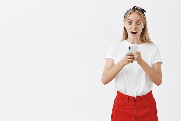 Atrakcyjna, Nowoczesna Dziewczyna Za Pomocą Telefonu Komórkowego I Patrząc Zaskoczony Darmowe Zdjęcia
