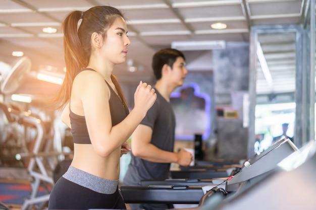 Atrakcyjna para działa na bieżni w siłowni. wspólne wypracowanie Premium Zdjęcia