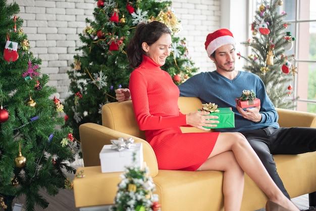Atrakcyjna para miłości rasy kaukaskiej świętuje boże narodzenie w domu Premium Zdjęcia
