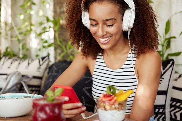 Atrakcyjna Pozytywna Afroamerykanka Z Kręconymi Włosami Nosi Słuchawki Przez Aplikację Mobilną I Rozmawia W Sieci, Podłączona Do Bezprzewodowego Internetu, Lubi Spędzać Wolny Czas, Czyta Dobre Wieści Darmowe Zdjęcia