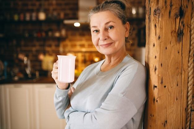 Atrakcyjna Radosna Starsza Kobieta Pozowanie W Pomieszczeniu, Ciesząc Się Gorącą świeżą Kawą Z Filiżanki Rano. Darmowe Zdjęcia