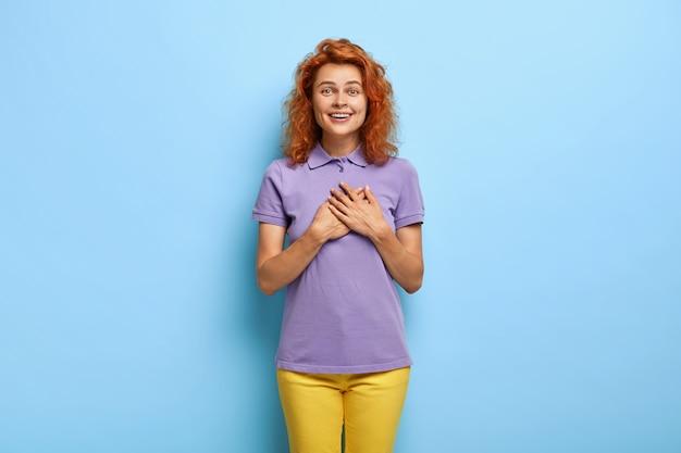 Atrakcyjna Ruda Dziewczyna Przyciska Dłonie Do Piersi, Czuje Wdzięczność Darmowe Zdjęcia