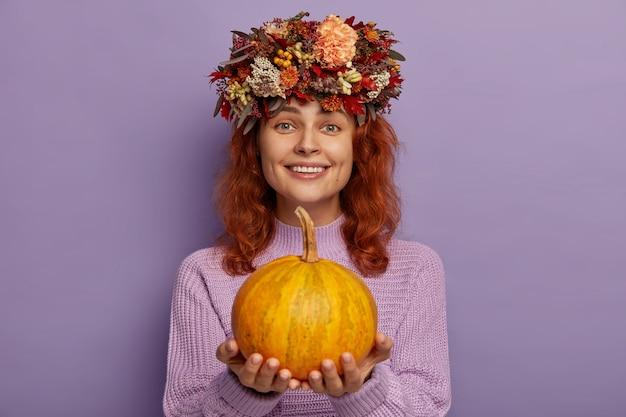 Atrakcyjna Ruda Kobieta Nosi Jesienny Wianek, Trzyma Dojrzałą Dynię, Nosi Fioletowy Sweter. Darmowe Zdjęcia