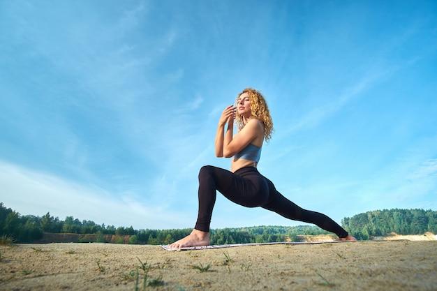 Atrakcyjna Rudzielec Kędzierzawa Kobieta ćwiczy Joga Outdoors Premium Zdjęcia