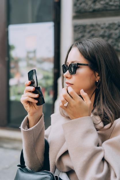 Atrakcyjna seksowna kobieta patrzy w małe lustro i koryguje makijaż Darmowe Zdjęcia