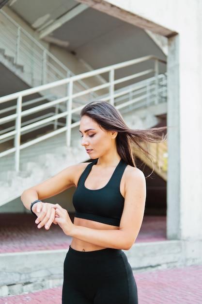 Atrakcyjna Sportowa Kobieta W Odzieży Sportowej Używa Inteligentnego Zegarka Na Zewnątrz W środowisku Miejskim Premium Zdjęcia