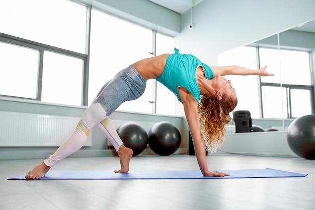 Atrakcyjna sportsmenka robi ćwiczenia na podłodze w nowoczesnym studio podniebień piękna, sportowa dziewczyna utyka i wyciąga nogi i ręce Premium Zdjęcia