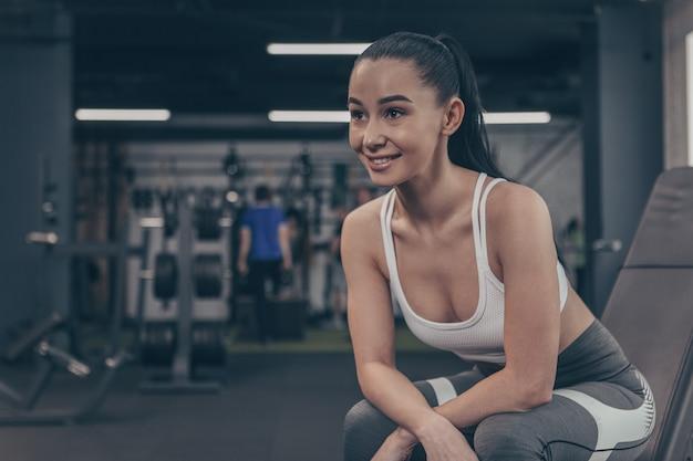 Atrakcyjna sportsmenka uśmiechając się wesoło, odwracając wzrok, relaksując się na siłowni Premium Zdjęcia