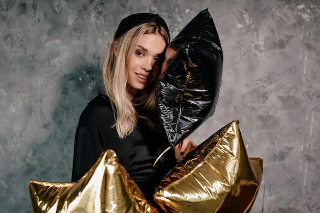 Atrakcyjna, Stylowa Dziewczyna O Blond Włosach Ubrana W Czarne Ubrania Przygotowujące Się Do Wigilii Darmowe Zdjęcia