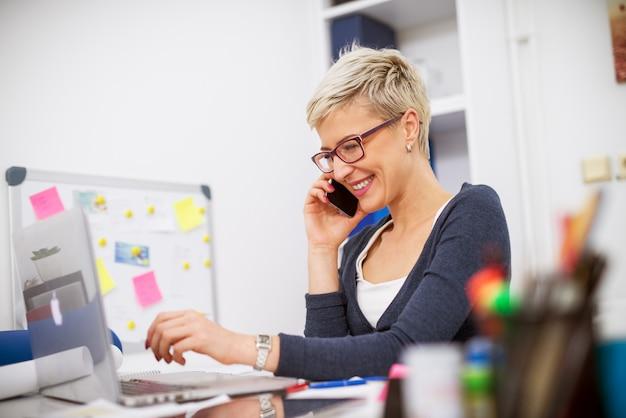 Atrakcyjna, Urocza Blond Kobieta Biznesu Z Krótkimi Włosami Rozmawia Przez Telefon, Siedząc Przy Biurku I Pracując Na Laptopie. Premium Zdjęcia