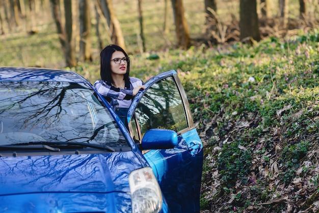 Atrakcyjne dziewczyny kierowcy wygląda z otwartych drzwi samochodu Premium Zdjęcia