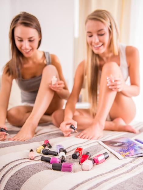 Atrakcyjne kobiety lakierują paznokcie u stóp na łóżku w domu. Premium Zdjęcia