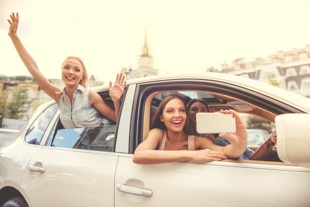 Atrakcyjne szczęśliwe dziewczyny w eleganckich ubraniach i słońc szkłach. Premium Zdjęcia