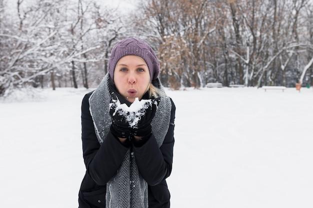 Atrakcyjnej młodej kobiety podmuchowy śnieg w zimy naturze Darmowe Zdjęcia