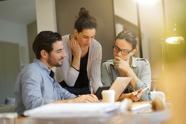 Atrakcyjni koledzy patrzeje pomysły w co pracującej przestrzeni Premium Zdjęcia