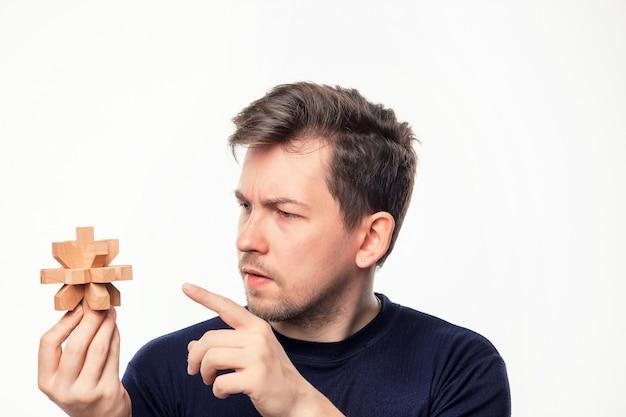 Atrakcyjny 25-letni Biznesmen Patrząc Zdezorientowany W Drewniane Układanki. Darmowe Zdjęcia