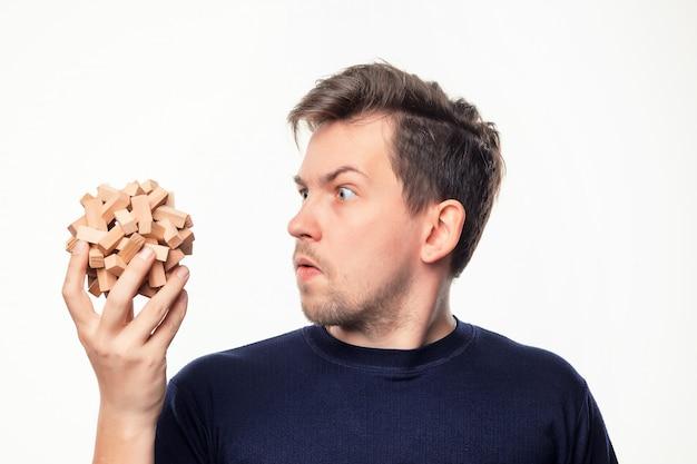 Atrakcyjny 25-letni Mężczyzna Patrząc Na Drewniane Puzzle. Darmowe Zdjęcia