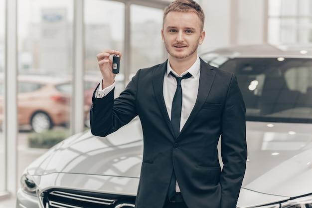 Atrakcyjny biznesmen kupuje nowy samochód przy przedstawicielstwem handlowym Premium Zdjęcia