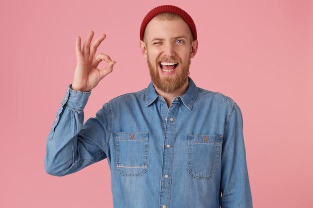 Atrakcyjny Brodaty Mężczyzna W Czerwonej Czapce Z Wymodelowanej Dżinsowej Koszuli, Zadowolony Wyraz Twarzy, Pokazuje Znak W Porządku, Czuje Się Zadowolony Po Spotkaniu, Odizolowany. Wyraz Twarzy Człowieka, Mowa Ciała Darmowe Zdjęcia