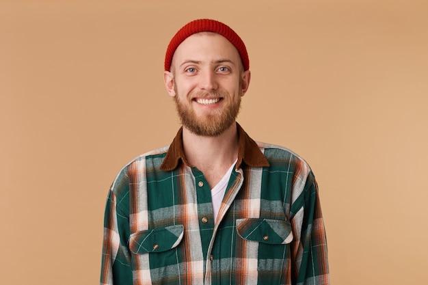 Atrakcyjny Brodaty Mężczyzna W Czerwonym Kapeluszu Z Szerokim Uśmiechem Pokazujące Zdrowe Zęby Darmowe Zdjęcia