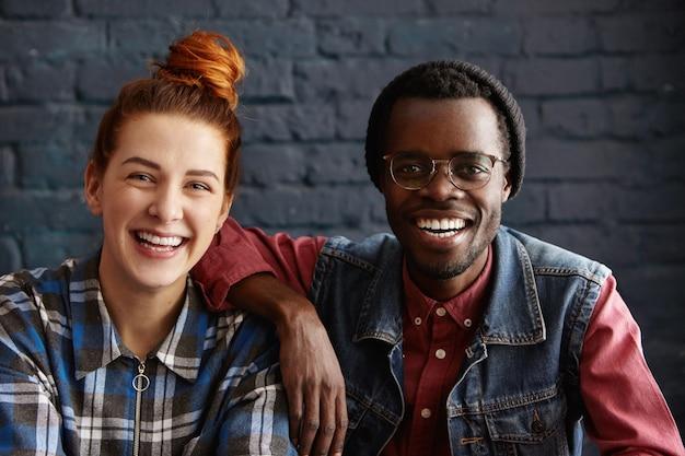 Atrakcyjny Mężczyzna Afroamerykanów W Kapeluszu I Okularach Opierając Ramię Na Ramieniu Z Pięknym Młodym Rudowłosym Darmowe Zdjęcia