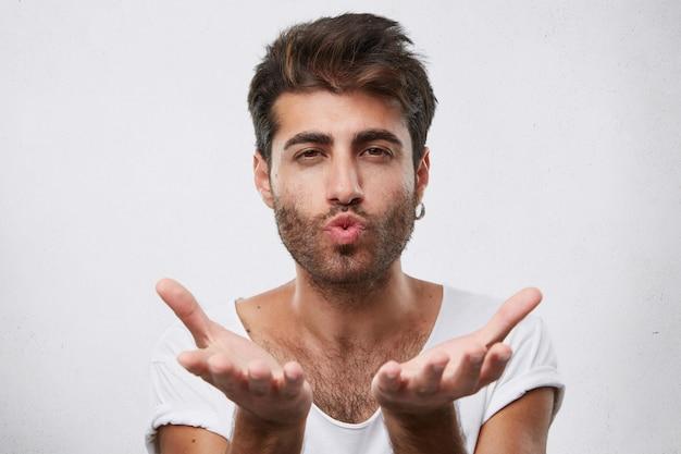 Atrakcyjny Mężczyzna Macho Z Ciemnymi Włosami I Brodą Całuje Cię I Trzyma Ręce Przed Sobą. Atrakcyjny Brunet Flirtuje Wysyłając Buziaka Darmowe Zdjęcia