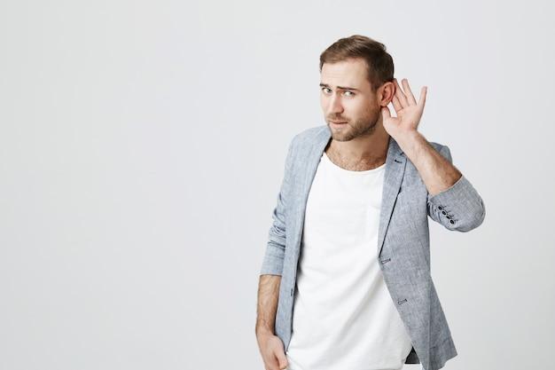 Atrakcyjny Mężczyzna Trzyma Rękę W Pobliżu Ucha Prosząc O Powtórzenie, Próbując Usłyszeć Darmowe Zdjęcia