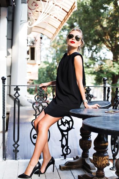 Atrakcyjny Model W Czarnej, Krótkiej Sukience Oparty O Stół Na Tarasie. Ona Patrzy Do Kamery. Darmowe Zdjęcia