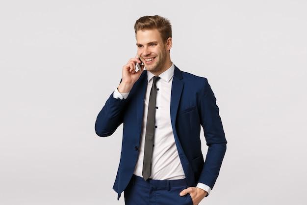 Atrakcyjny, Odnoszący Sukcesy I Zamożny Młody Kaukaski Biznesmen W Garniturze, Rozmawia Przez Telefon, Trzyma Smartfon Przy Uchu, Dzwoni Do Zagranicznych Partnerów Biznesowych, Omawia Personel Korporacyjny, Białe Tło Premium Zdjęcia