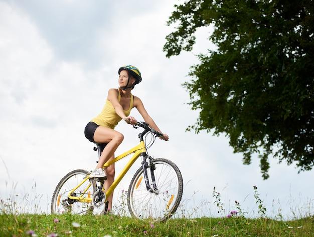 Atrakcyjny Szczęśliwy Kobiety Rowerzysta Jedzie Na żółtym Halnym Rowerze Na Trawiastym Wzgórzu Premium Zdjęcia