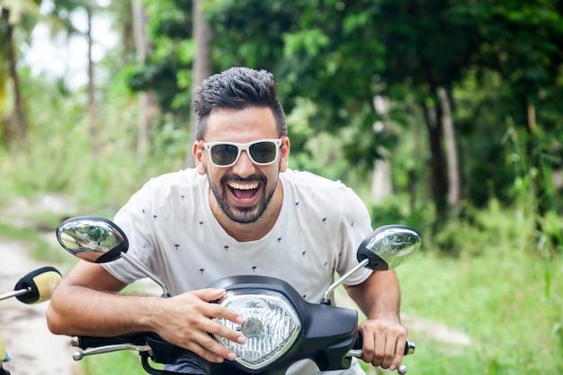 Atrakcyjny szczęśliwy uśmiechnięty mieszany biegowy młody człowiek na motocyklu w dżungli, wakacje, szczęście Premium Zdjęcia