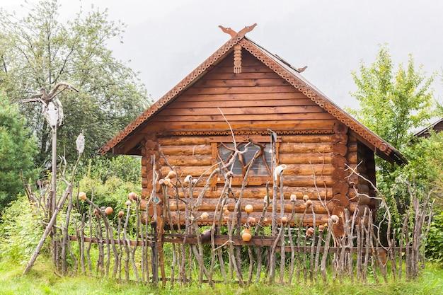 Autentyczny Drewniany Dom Z Wazą Ceramiczną, Okiennicami I Stojakami Na Okna Premium Zdjęcia