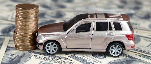 Autko w wypadku na 100 dolarowych banknotach i stosie złotych monet Premium Zdjęcia