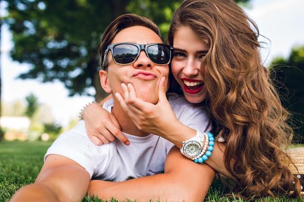 Autoportret śmiesznej Pary Leżącej Na Trawie W Parku Latem. Dziewczyna Z Długimi Kręconymi Włosami, Czerwonymi Ustami I Młody Facet W Okularach Przeciwsłonecznych Aping Do Kamery. Darmowe Zdjęcia
