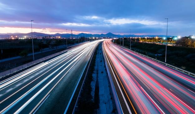 Autostrada O Zachodzie Słońca, Pojazdy Jadące W Dwóch Kierunkach Pozostawiają Smugi światła Premium Zdjęcia
