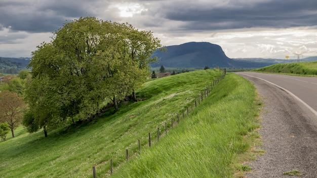 Autostrada Otoczona Zielonymi Polami I Górami Pod Ponurym Niebem Darmowe Zdjęcia