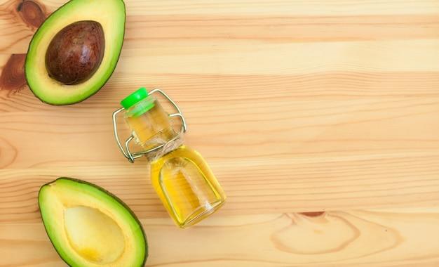 Avocado i avocado olej w butelce na drewnianym tle. Premium Zdjęcia