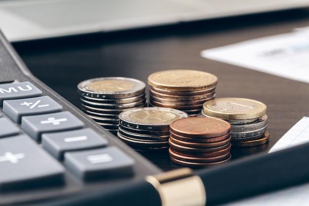 Awanse, finanse, ekonomia i dom - zbliżenie kalkulatora do liczenia pieniędzy i robienia notatek w domu Premium Zdjęcia