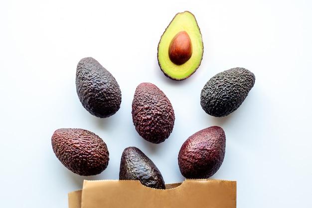 Awokado Na Białym Tle. Owoce Są Rozrzucone Na Stole. Składnik Prawidłowego Odżywiania Premium Zdjęcia
