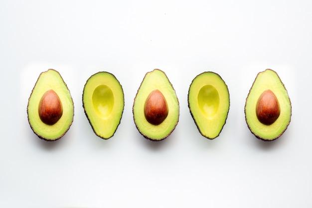 Awokado Na Białym Tle. Wytnij Awokado Leży W Jednej Linii. Owoce Rozsypują Się Na Stole Premium Zdjęcia