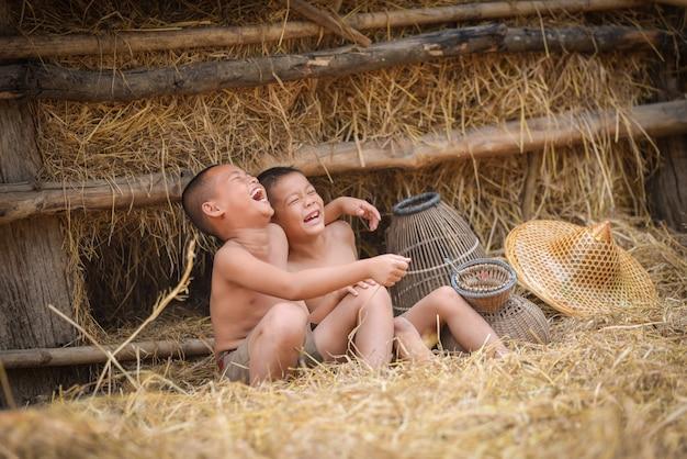 Azja dziecko śmiech chłopiec przyjaciela szczęśliwy śmieszny śmiać się i uśmiech przy wsią Premium Zdjęcia