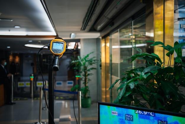 Azjaci Czekają Na Kontrolę Temperatury Ciała Przed Wejściem Do Budynku Pod Kątem Epidemii Grypy Covid19 Lub Grypy Koronowej W Biurze Za Pomocą Termoskopu Lub Kamery Termowizyjnej Na Podczerwień Premium Zdjęcia