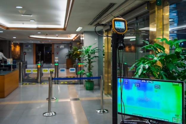Azjaci Czekają Na Sprawdzenie Temperatury Ciała Przed Wejściem Do Budynku Za Pomocą Termoskopu Lub Kamery Termowizyjnej Premium Zdjęcia